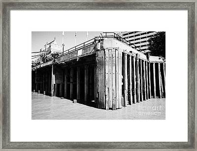 concrete piles and wooden stanchions on thames riverbank London England UK Framed Print by Joe Fox