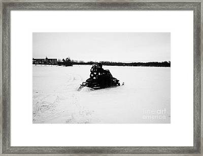 couple on a snowmobile going cross country Kamsack Saskatchewan Canada Framed Print