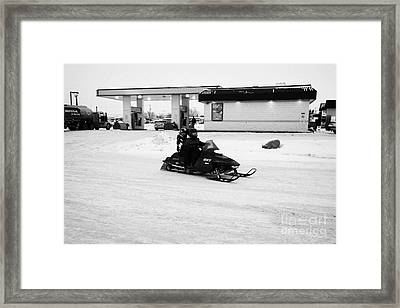 couple on a snowmobile leaving a gas station Kamsack Saskatchewan Canada Framed Print