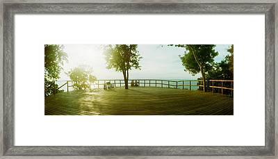 Couple Overlooking The Ocean At Sunset Framed Print by Panoramic Images