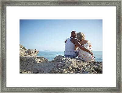 Couple Sitting On A Rock Framed Print