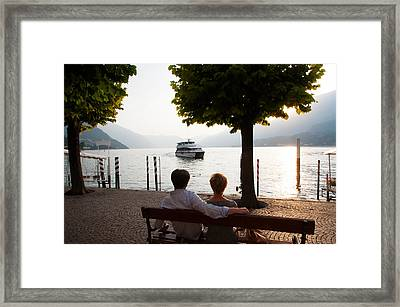 Couple Sitting On Bench And Watching Framed Print by Panoramic Images