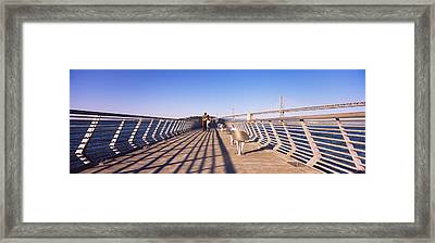 Couple Walking On A Pier, Bay Bridge Framed Print by Panoramic Images