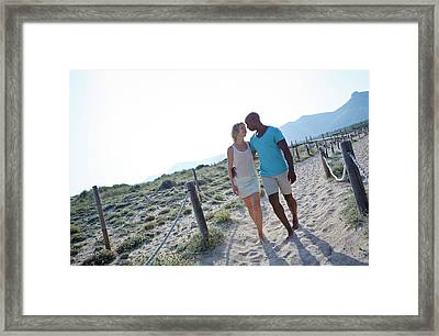Couple Walking On Sand On Holiday Framed Print