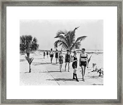 Couples Strolling Along The Pathway On The Beach. Framed Print by -