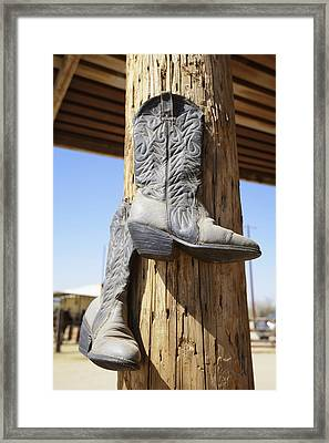 Cowboy Boots Hanging From A Post At A Framed Print by Peter Carroll