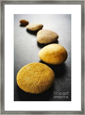 Curving Line Of Brown Pebbles On Dark Background Framed Print by Colin and Linda McKie