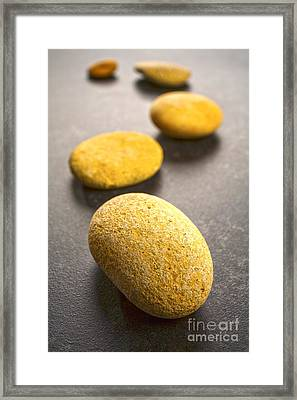 Curving Line Of Stones Pebbles On Dark Background Vertical Framed Print by Colin and Linda McKie