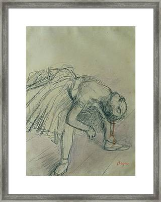 Dancer Fixing Her Slipper Framed Print by Edgar Degas