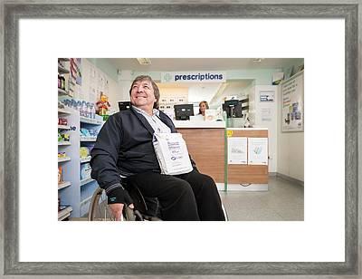 Disabled Man In Pharmacy Framed Print by Jim Varney