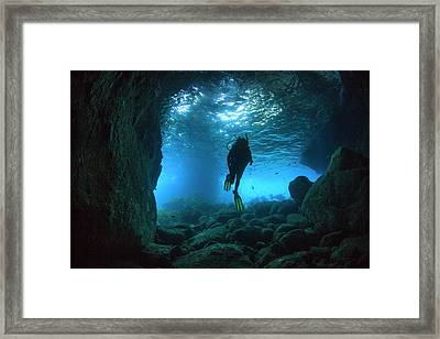 Diver Swimming Through A Sea Cave Framed Print