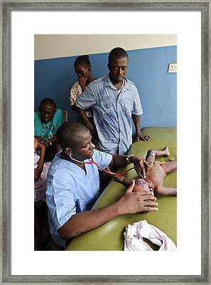 Doctor Examining A Baby Framed Print