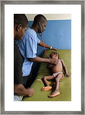 Doctor Examining A Child Framed Print by Matthew Oldfield