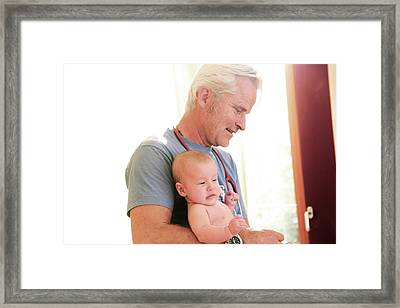Doctor Holding Baby Framed Print by Gombert, Sigrid