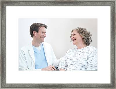 Doctor Smiling At Woman Patient Framed Print by Science Photo Library