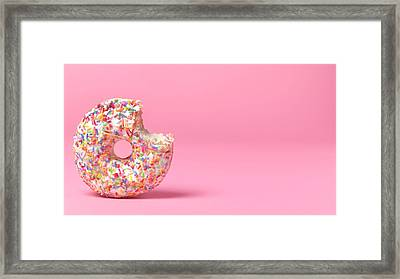 Doughnut On Pink With Bite Out Framed Print by Peter Dazeley