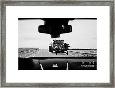 driving behind combine harvester on road in Saskatchewan Canada Framed Print by Joe Fox