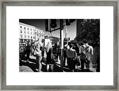 early morning commuters waiting to cross the road pedestrian crossing London England UK Framed Print by Joe Fox