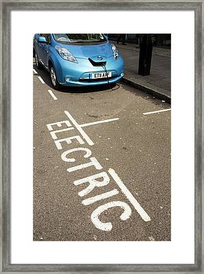 Electric Car At A Recharging Station Framed Print