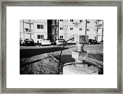 electric power connection for engine block heaters in residential parking bay outside homes in Saska Framed Print by Joe Fox