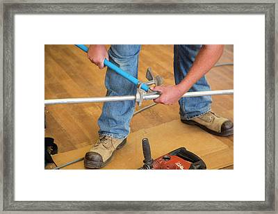 Electrician Using A Pipe Bender Framed Print by Jim West