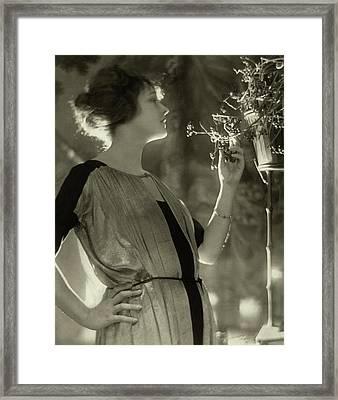 Elsie Ferguson Looking At A Pot Plant Framed Print by Baron Adolphe De Meyer