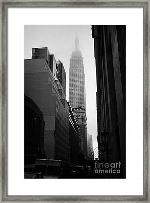 empire state building shrouded in mist in amongst dark cold buildings on 33rd Street new york city Framed Print by Joe Fox