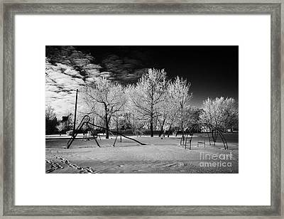 empty childrens playground with hoar frost covered trees on street in small rural village of Forget  Framed Print by Joe Fox