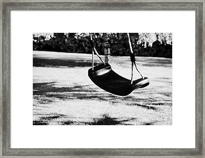 Empty Plastic Swing Swinging In A Garden In The Evening Framed Print