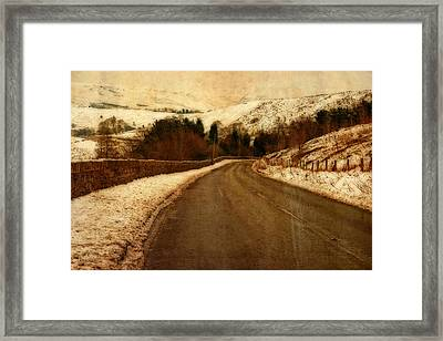 Empty Road Through Snow Covered Yorkshire Moors Framed Print by Ken Biggs