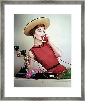 Evelyn Tripp Holding Telephones Framed Print by Erwin Blumenfeld