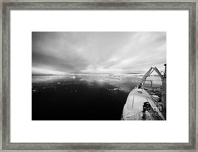 expedition ship with lifeboat covered in snow moored in Fournier Bay on Anvers Island Antarctica Framed Print by Joe Fox