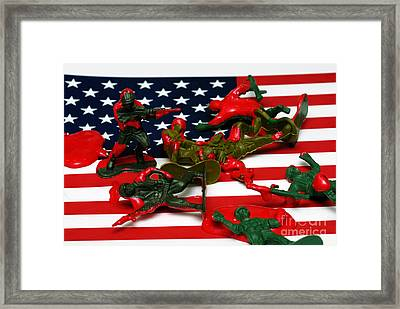 Fallen Toy Soliders On American Flag Framed Print