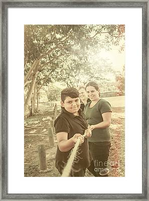 Family Playing Tug Of War At Park Framed Print