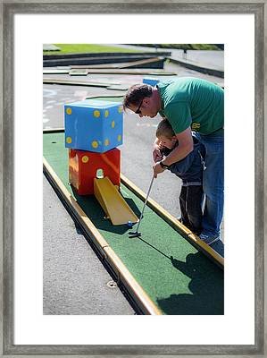 Father Helping Son To Play Mini Golf Framed Print