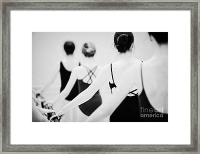Female Teenage Ballet Students Holding On To A Ballet Barre At A Ballet School In The Uk Framed Print