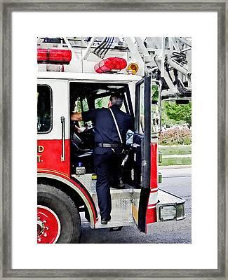 Fireman Climbing Into Fire Truck Framed Print by Susan Savad