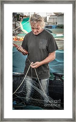 fisherman mending nets on Anzio harbour Framed Print