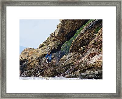 Framed Print featuring the photograph Fisherman On Rocks  by Sarah Mullin