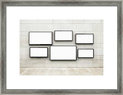 Flat Screens Hanging On A Wall Framed Print by Jorg Greuel