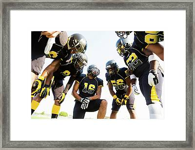 Football Team Huddled During Time Out Framed Print by Asiseeit