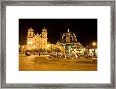 Fountain Lit Up At Night At A Town Framed Print