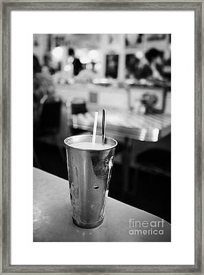 fresh strawberry milkshake served in a metal cup in a diner in Saskatchewan Canada Framed Print by Joe Fox
