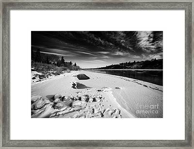 frozen river bank of the south saskatchewan river in winter flowing through downtown Saskatoon Saska Framed Print by Joe Fox