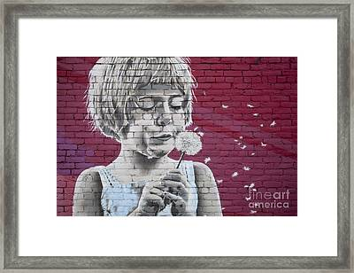 Girl Blowing A Dandelion Framed Print