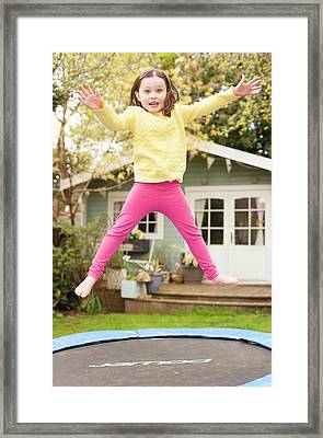 Girl Bouncing On A Trampoline Framed Print