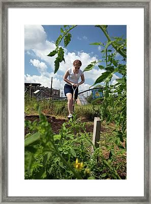 Girl Digging In A Garden Framed Print