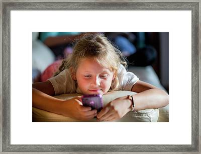 Girl Lying On Front Using A Smartphone Framed Print by Samuel Ashfield