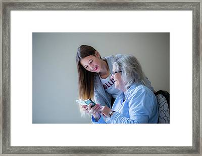 Girl Showing Grandmother Smartphone Framed Print by Samuel Ashfield