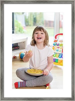 Girl Sitting On Floor Eating French Fries Framed Print by Aberration Films Ltd